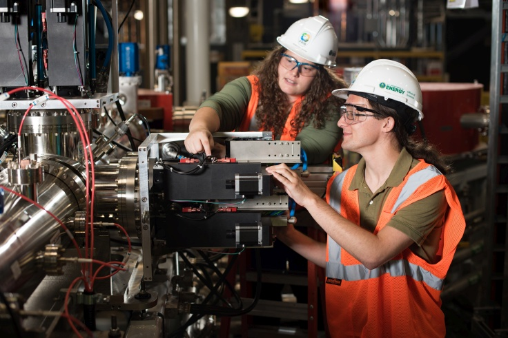 Graduate Assistant Christopher Richard (right) and Diagnostic Research Scientist Rebecca Shane inspect the controls for a system used to select ion-beam charge states.