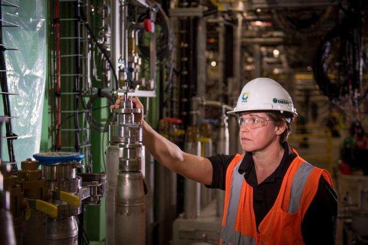 Shelly Jones, FRIB cryogenic fabrication group leader, inspects cryogenic equipment that is part of FRIB's linear accelerator.