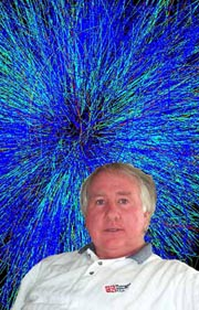 Gary Westfall in front of a detector image displaying a collision of gold nuclei
