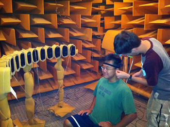 Tom is inserting tiny probe microphones into Cho's ear canals. Later, Cho will localize sounds from the 13 loudspeakers in the anechoic room, and his responses will be compared with recordings from the microphones photo