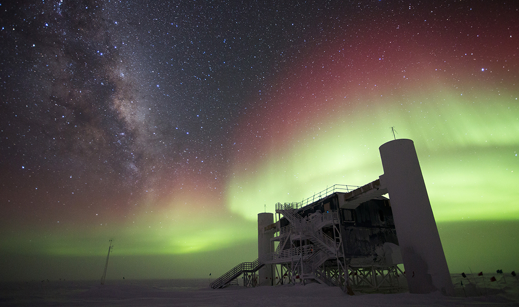 The IceCube Neutrino Observatory encompasses a cubic kilometer of ice under the surface of the Antarctic icecap at the South Pole. This is a photo of the laboratory building at the surface on a winter night with auroral activity.