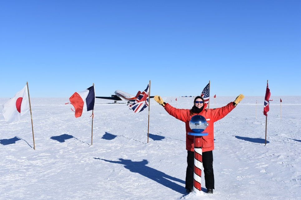 Rysewyk at the ceremonial South Pole with a Basler plane in the background. The location of the ceremonial South Pole stays the same; however, the geographical South Pole moves a little bit every year. In 2018, it moved 33 feet!