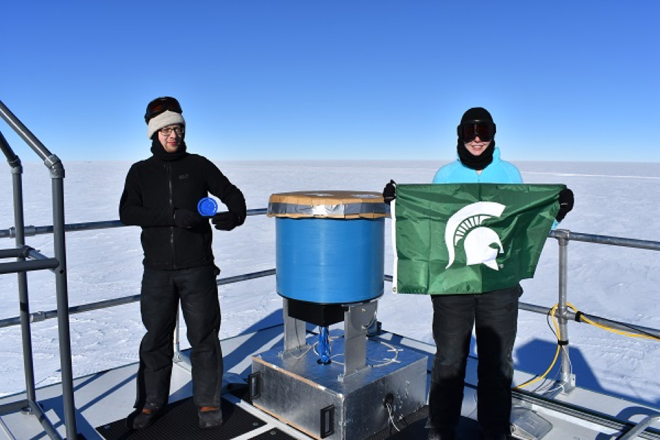 Devyn Rysewyk (R) stands next to Martin Rongen, of RWTH Aachen University in Germany and Rysewyk's teammate, and the finished particle detector prototype atop the IceCube Laboratory located at the Amundsen-Scott South Pole Station.
